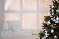 Julklappar i vita askar på ett fönster under en julgran Arkivfoton