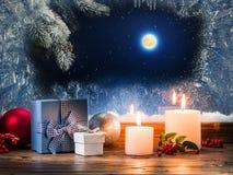 Julklappar med bränningstearinljuset på fönsterbrädan med PA Arkivbild