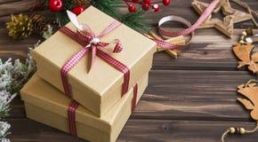 Julklappar med det festliga bandet och prydnader på träb Royaltyfria Bilder