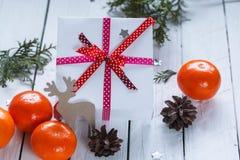 Julklappar med det röda bandet och tangerin Royaltyfri Bild