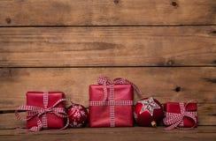 Julklappar med en röd vit kontrollerade bandet på gammalt trä Royaltyfri Fotografi