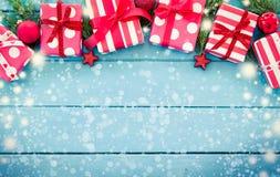 Julklappar med garnering på den blåa trätabellen Arkivbild