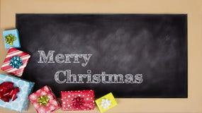 Julklappar som grupperas runt om en svart tavla Fotografering för Bildbyråer