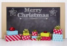 Julklappar som grupperas runt om en svart tavla Arkivfoto