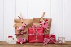 Julklappar som slås in i pappers- påsar med kontrollerad röd vit Arkivfoto