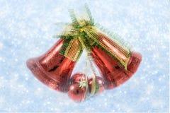 Julklockor med pilbågen på skinande bakgrundssnöflingor Arkivfoto