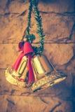 Julklockor som hänger på bakgrunden för tegelstenvägg arkivbild