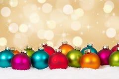 Julkort guld- bakgrundsgarnering för många färgrika bollar Arkivfoto