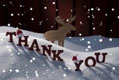 Julkort med älgen, hatten och snö, tacka dig, snöflingor Arkivbild