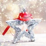 Julkort med den festliga stjärnan, snö och det röda bandet på abstrac Arkivfoton