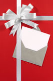 Julkort med den vita gåvabandpilbågen på röd pappers- bakgrundslodlinje Arkivbild