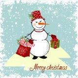 Julkort med en snowman och gåvor Arkivbild