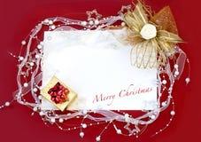Julkort med garneringen på röd bakgrund Arkivbilder