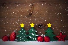 Julkort med gröna träd och röda bollar, snö, snöflingor Arkivbilder