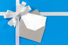 Julkort med gåvabandpilbågen i vit satäng på bakgrund för blått papper Arkivfoton