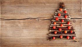 Julkort med naturliga garneringar på träbakgrund Royaltyfri Fotografi