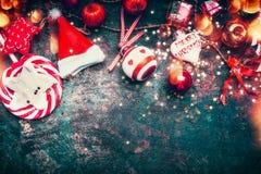 Julkort med röd garnering, jultomtenhatten, bollar och godisen på mörker - blå tappningbakgrund, bästa sikt royaltyfria bilder