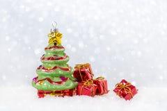 Julkort med trädet och gåvor i snö, snowflackesbokeh Arkivfoton