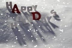 Julkort med vita och röda bokstäver, lyckliga ferier, snö Royaltyfria Bilder