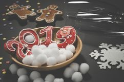 Julkort: på en träplatta är röda ljust rödbrun kakor i formen av nummer 2019 och vita runda snöflingor royaltyfri bild