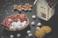 Julkort: på en träplatta är röda ljust rödbrun kakor i formen av nummer 2019 och vita runda snöflingor royaltyfria bilder