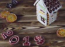 Julkort på röda nummer 2019 för träbakgrundspepparkaka med skivor av det orange och vita pepparkakahuset med ett brunt tak royaltyfri bild