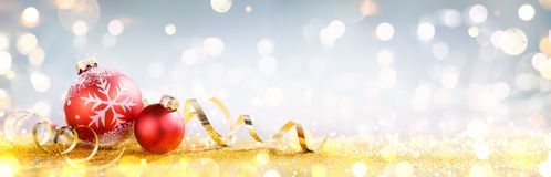 Julkort - röda bollar på guld- banderoller arkivfoton