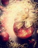 Julkortet med den röda tappningstruntsaken, det guld- bandet och garnering på gnistrande semestrar bakgrund arkivbilder