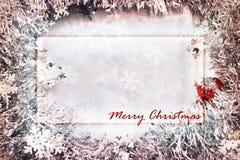 Julkorthälsningen med den rectangled ramen som omges av snöflingan, blänker royaltyfria foton