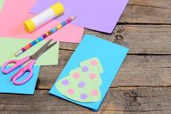 Julkorthandbok moment Det pappers- julhälsningkortet, blyertspennan, limpinne, färgade papper, sax på wood bakgrund Royaltyfri Bild