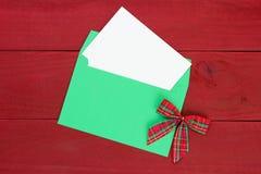 Julkortkuvert och bokstav med pilbågen och röd wood bakgrund royaltyfri fotografi