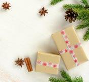 Julkortsammansättning med gåvaaskar som slås in i kraft papper, gran förgrena sig med kotten arkivfoton