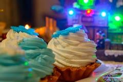 Julkräm bakar ihop och undersöker tätt upp på tabellen med kulöra ljus Royaltyfri Bild