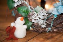 Julkrans av filialer på pälshuden med företaget av en snögubbe och en hund med en stearinljus i bakgrunden royaltyfria bilder