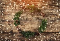 Julkrans av granfilialer, kottar på träbakgrund med snöflingor royaltyfria bilder