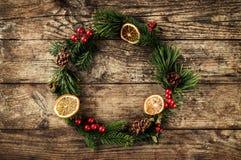 Julkrans av granfilialer, kottar, röd garnering på träbakgrund med snöflingor royaltyfri bild