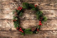 Julkrans av granfilialer, kottar, röd garnering på träbakgrund med snöflingor royaltyfri fotografi