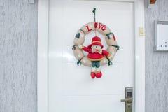 Julkrans med en snögubbe som hänger på dörren fotografering för bildbyråer
