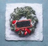 Julkrans med gröna granfilialer och det röda inramade tecknet och jultomtenhatt i snö på blå bakgrund, bästa sikt med den svart t arkivfoton