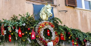 Julkrans och garneringar på fasad med skulptur av hästen royaltyfri bild
