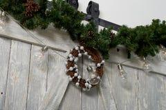 Julkrans som hänger på de massiva trädörrarna bolljulen isolerade white för mood tre Arkivfoto