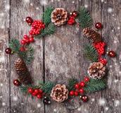 Julkransen av gran förgrena sig, kottar, röda garneringar på mörk träbakgrund royaltyfri bild