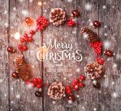 Julkransen av gran förgrena sig, kottar, röda garneringar på mörk träbakgrund arkivfoto