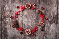 Julkransen av gran förgrena sig, kottar, röda garneringar på mörk träbakgrund arkivfoton