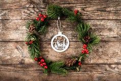 Julkransen av granfilialer, sörjer kottar, bär och garnering av trä på lantlig bakgrund Tema för Xmas och för lyckligt nytt år royaltyfri fotografi