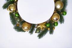 Julkransen på vit bakgrund, baner med gran förgrena sig och klumpa ihop sig ovanför sikt Färger är guld-, gröna och vita nytt Royaltyfri Bild