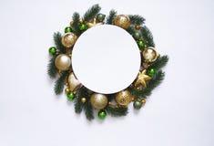 Julkransen på vit bakgrund, baner med gran förgrena sig och klumpa ihop sig ovanför sikt Färger är guld-, gröna och vita nytt Royaltyfri Foto