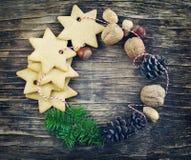 Julkransen som göras från kakor, muttrar, sörjer kottar, och gran förgrena sig Arkivfoton