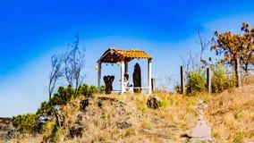 Julkrubba med änglar och oskulden av Guadalupe på en kulle med ett kors på sidan arkivbilder