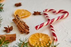 Julkryddor - kanelbruna pinnar, anisstjärnor, torkade apelsiner med röd hjärta av godiskottar, och suddig grön gran förgrena sig Royaltyfri Bild